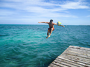 young man jumps off a pier while kicking a football Photographed in Caye Caulker, Belize