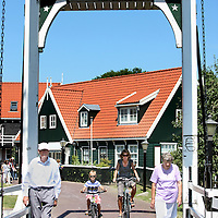 Nederland, Marken , 23 juni 2010..Marken (plaatselijk: Mereke) is een voormalig eiland in de Zuiderzee, tegenwoordig Markermeer dat sinds 1957 via een dijk met het vasteland verbonden is. Het behoort tot de gemeente Waterland in de provincie Noord-Holland..Marken vormt in wezen één leef- en woonplaats, maar is opgedeeld in diverse buurtschappen. Oorspronkelijk lagen die ook echt los van elkaar. Tegenwoordig liggen sommige buurten aan elkaar, zoals Havenbuurt, Kerkbuurt en Kets..Marken is a former island in the Zuiderzee, now Markermeer  and connected through a dike to the mainland since 1957. The natives are still in costume, and that attracts tourists as are the green wooden houses.