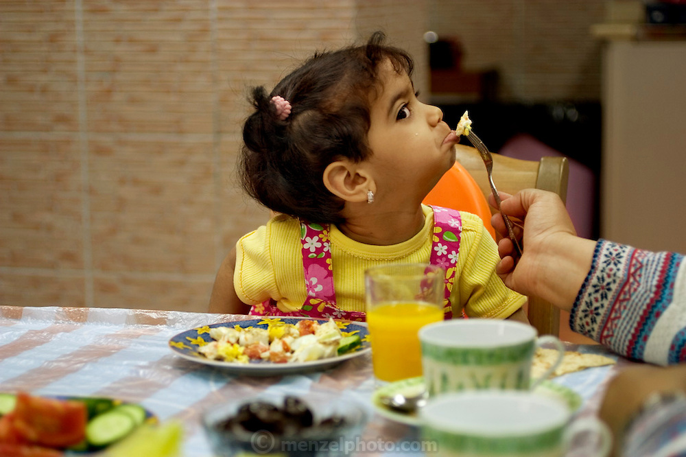 (MODEL RELEASED IMAGE). The diverse breakfast mix of Western (tomato omelet) and Eastern (cucumber salad, olives) food found in Kuwait is not enough to tempt fussy 2-year-old Rayyan Al Haggan. Hungry Planet: What the World Eats (p. 201).