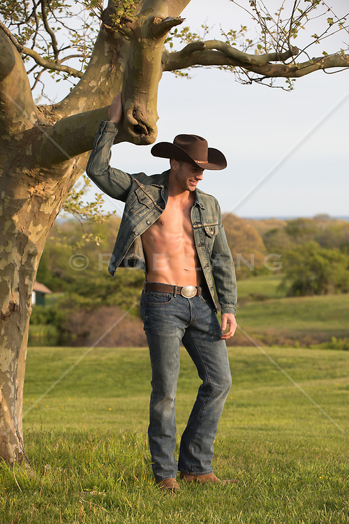 Hot muscle cowboy without a shirt on a ranch
