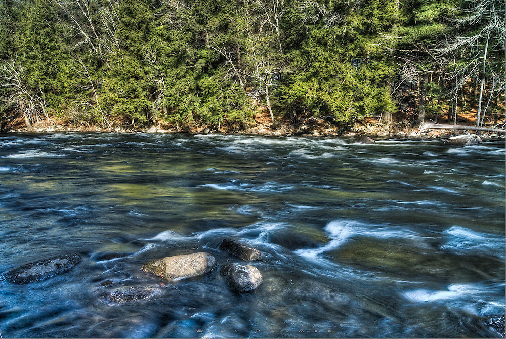Schroon River, Adirondacks, NY.<br /> Three dry boulders caught my eye and  became the foreground of this scene on the Schroon River, which reflected the green of late afternoon light that fell on pines lining the far bank.  A polarizer left some clarity under the water, belying how deep this river actually is. I processed two exposures about 2/3 of a stop apart, in Photomatix, trying to get some more texture and saturation in the water (although I left the actual Saturation slider alone, adding no color other than the raw takes).