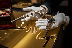 © Licensed to London News Pictures. 06/07/2015. London, UK.  A Sotheby's technician shows a pair of bespoke gold-encrusted pistols made by the celebrated gunsmith Jean Lepage for Napoleon's three year old son (est. £800k to £1.2m at the preview of Old Masters, British Paintings and Masterworks from the collection of Castle Howard at Sotheby's ahead of the auction on July 8. Photo credit : Stephen Chung/LNP