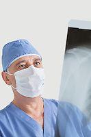 Senior male surgeon examining x-ray over gray background