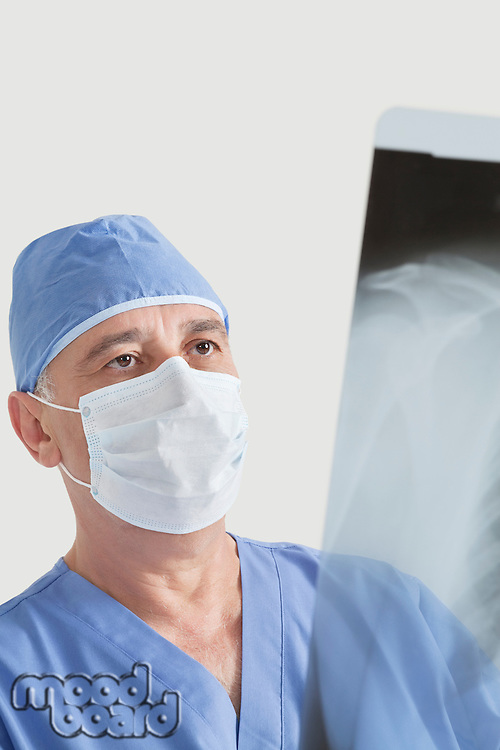 Senior male surgeon examining x-ray over gray background