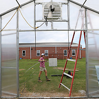 """Amanda Huels carries a handful of """"wiggle wire"""" to the south side of the new greenhouse to secure the plastic wrap as she helps finish the house at Lawndale Elementary School."""
