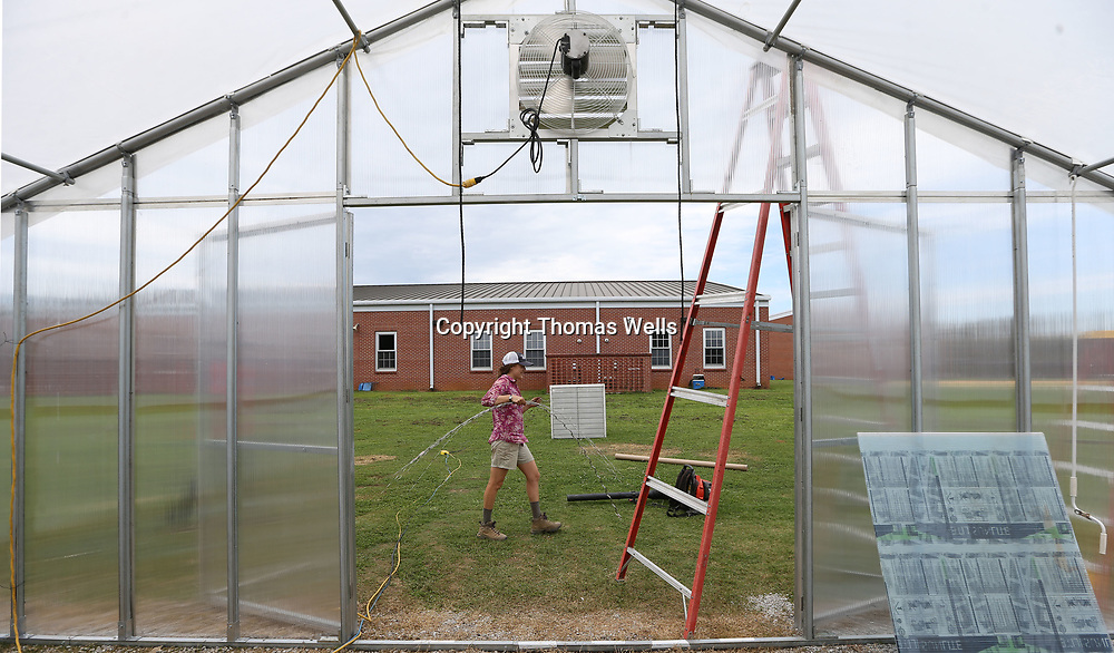 "Amanda Huels carries a handful of ""wiggle wire"" to the south side of the new greenhouse to secure the plastic wrap as she helps finish the house at Lawndale Elementary School."