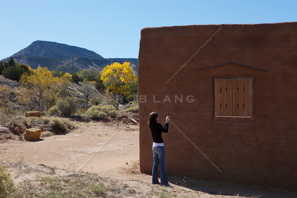 woman in Abiquiu, New Mexico photographing an adobe building