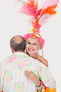 Portrait of senior couple in Brazilian outfits dancing over gray background