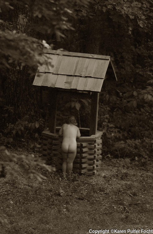 A little girl enjoys playing in a country well.