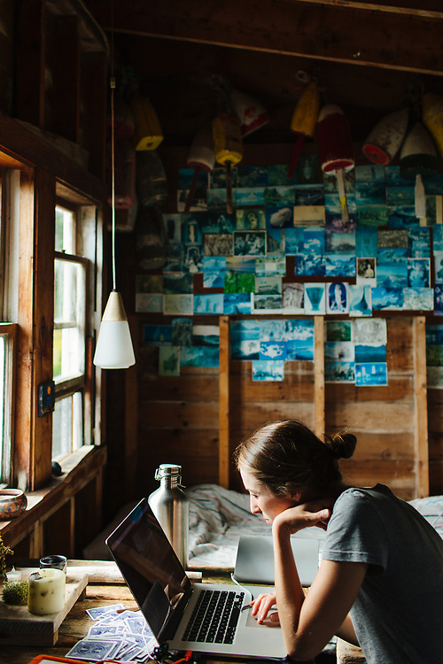 Woman Sitting at Table Using Laptop in Cabin, Vinalhaven, Maine.