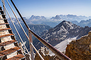 "From Rifugio Guido Lorenzi on Monte Cristallo in the Ampezzo Dolomites, look northeast across blue ridges of the Sesto Dolomites (Dolomiti di Sesto, or Sexten/Sextner/Sextener Dolomiten) to the pyramids of Tre Cime di Lavaredo (Italian for ""Three Peaks of Lavaredo,"" called Drei Zinnen or ""Three Merlons"" in German). A lift to Forcella Staunies on Monte Cristallo gives unforgettable views over the Dolomites mountains (part of the Southern Limestone Alps) near Cortina d'Ampezzo, in the Province of Belluno, Veneto region, Italy, Europe. Monte Cristallo lies within Parco Naturale delle Dolomiti d'Ampezzo. Directions: From Cortina, drive 6km east on SR48 to the large parking lot for Ski Area Faloria Cristallo Mietres (just west of Passo Tre Croci Federavecchia). Take a chair-lift from Rio Gere to Son Forca (rising from 1698m to 2215m). Then take the old style ovovia (egg-shaped) Gondellift Forcella Staunies to Rifugio Guido Lorenzi (2932m) for astounding views. Climbers enjoy spectacular via ferrata routes here. Cortina gained worldwide fame after hosting the 1956 Winter Olympics. UNESCO honored the Dolomites as a natural World Heritage Site in 2009."