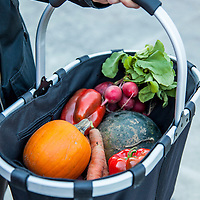 Closeup of a shopper holding a cloth shopping basket of fresh, local vegetables and fruit from a farmers market.