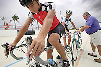 Daniel Jimenez, 17, left, is waiting to start his training session while his coach Carlos Lavorde, right, is teaching Carlos Rocha, 17,  at the Bryan Piccolo park's velodrome on Monday June 29, 2009. Staff photo/Cristobal Herrera.