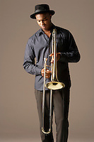 Trombonist standing wearing hat looking at trombone