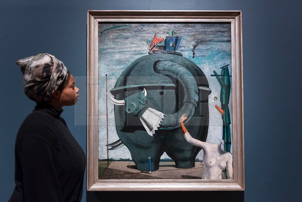 """© Licensed to London News Pictures. 04/06/2018. LONDON, UK. A gallery staff member views """"Celebes"""", 1921, by Max Ernst at a preview of """"Aftermath:  Art in the wake of World War One"""" at Tate Britain.  The exhibition marks 100 years since the end of the First World War, exploring the impact of the conflict on British, German, and French art in over 150 works from 1916 to 1932.  The show runs 5 June to 23 September 2018.  Photo credit: Stephen Chung/LNP"""