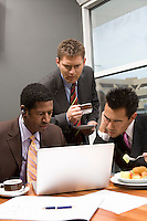 Three business men using laptop in office
