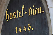 Detail of lettering on the porch of the main entrance on the external facade of Les Hospices de Beaune, or Hotel-Dieu de Beaune, a charitable almshouse and hospital for the poor, built 1443-57 by Flemish architect Jacques Wiscrer, and founded by Nicolas Rolin, chancellor of Burgundy, and his wife Guigone de Salins, in Beaune, Cote d'Or, Burgundy, France. The buildings, set around an internal courtyard, are in Northern Renaissance and Flamboyant Gothic style, with half-timber galleries, ornate rooftops with Burgundian glazed tiles in geometric patterns and dormer windows. The hospital was run by the nuns of the order of Les Soeurs Hospitalieres de Beaune, and remained a hospital until the 1970s. The building now houses the Musee de l'Histoire de la Medecine, or Museum of the History of Medicine, and is listed as a historic monument. Picture by Manuel Cohen