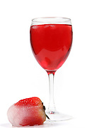 Cutout of a frozen Strawberry in an ice cube and a glass of strawberry juice on white background
