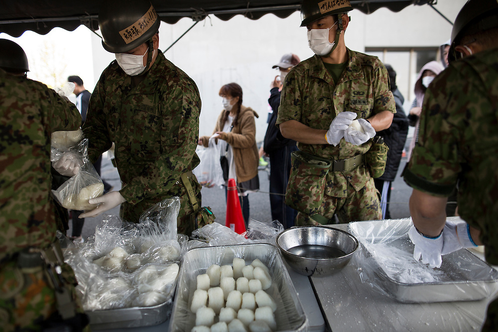 KUMAMOTO, JAPAN - APRIL 20: Self-Defense Forces personnel distribute food for evacuees early morning on Wednesday April 20, 2016 in Mashiki Gymnasium evacuation center, Kumamoto, Japan. As of April 45 people were confirmed dead after strong earthquakes rocked Kyushu Island of Japan. Nearly 11,000 people are reportedly evacuated after the tremors Thursday night at magnitude 6.5 and early Saturday morning at 7.3.<br /> <br /> Photo: Richard Atrero de Guzman