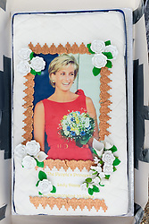 © Licensed to London News Pictures. 29/08/2017. London, UK. British Royal family fans make a cake featuring the late Princess Diana outside the Golden Gates of Kensington Palace on the eve of the 20th anniversary her death. The Princess died in a car crash in Paris, France, on 31st August 1997. Photo credit: Ray Tang/LNP