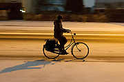 Een fietser rijdt 's avonds door de sneeuw. De weg is nog niet gestrooid