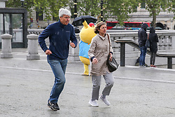 © Licensed to London News Pictures. 04/05/2019. London, UK. A couple runs for shelter as it starts to rain suddenly in Trafalgar Square. Photo credit: Dinendra Haria/LNP
