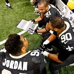 November 25, 2012; New Orleans, LA, USA; New Orleans Saints defensive end Will Smith (91) and teammates defensive end Turk McBride (90) and defensive end Cameron Jordan (94) review pictures on the sideline during the first half of a game against the San Francisco 49ers at the Mercedes-Benz Superdome. Mandatory Credit: Derick E. Hingle-US PRESSWIRE