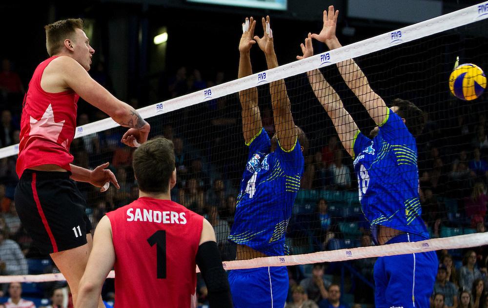 Daniel Cornelius Jansen Vandoorn (11) of Canada spikes the ball versus Filip Cveticanin (4) and Andre Reis Lopes (18) of Portugal during a World League Volleyball match at the Sasktel Centre in Saskatoon, Saskatchewan Canada on June 26, 2016.