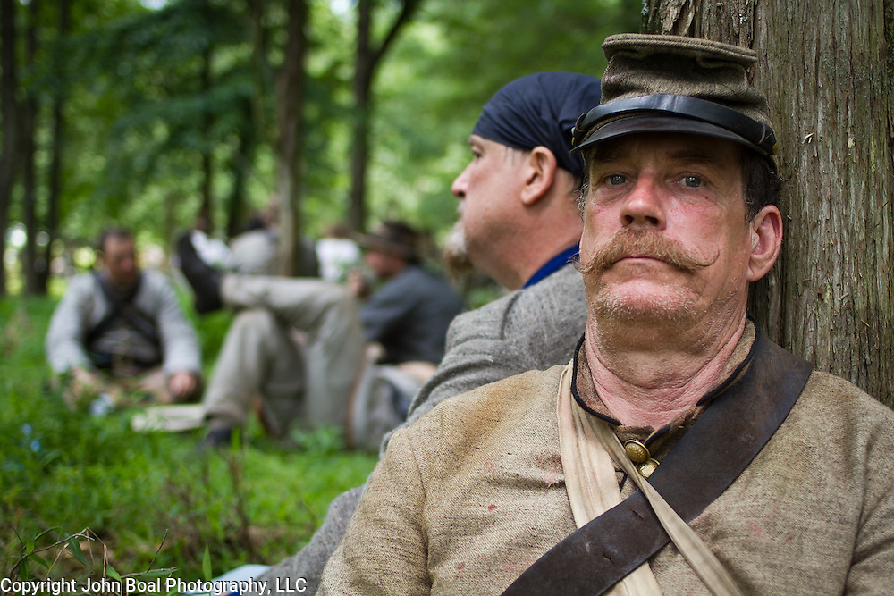John King, of Gillsville, Georgia, rests his head against a tree, prior to participating in a reenactment of Pickett's Charge, as part of the 47th North Carolina, during the Sesquicentennial Anniversary of the Battle of Gettysburg, Pennsylvania on Sunday, June 30, 2013.   A pivotal moment in the Civil War, over 50,000 soldiers were killed, wounded or missing after 3 days of battle from July 1-3, 1863.  Later that year, President Abraham Lincoln returned to Gettysburg to deliver his now famous Gettysburg Address to dedicate the cemetery there for the Union soldiers who died in battle.  John Boal photography