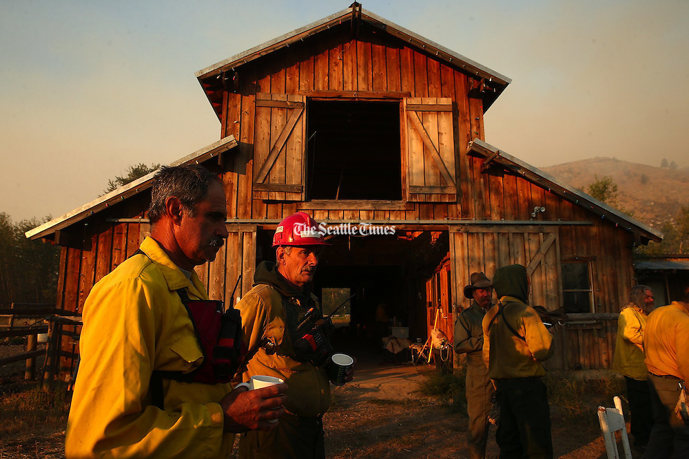 Firefighters gather at the home of a Twisp resident on Thursday, Aug. 20, 2015.<br />