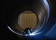 A worker welds a spot inside a section of a wind turbine tower at Trinity Structural Towers in Newton, Iowa on February 12, 2010.