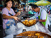 08 AUGUST 2018 - BANGKOK, THAILAND: A stand selling Pa Tong Go (fried Chinese dough sticks) at Khlong Toei Market in Bangkok. It is the largest market in Thailand. Pa Tong Go are common in Southeast Asia and are also called Youtiao, Chinese fried churros, Chinese cruller, Chinese oil stick, Chinese doughnut, or You Char Kway depending on where they're made and sold.    PHOTO BY JACK KURTZ