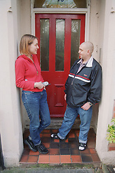 Resident of homeless hostel for people with learning difficulties standing on doorstep of hostel discussing progress with assistant manager,