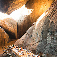 The table is set for a dinner inside of a cave at Spitzkoppe in Namibia.