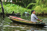 "17 NOVEMBER 2012 - BANGKOK, THAILAND:  A woman paddles her small canoe through a khlong or canal in the Thonburi section of Bangkok. Bangkok used to be known as the ""Venice of the East"" because of the number of waterways the criss crossed the city. Now most of the waterways have been filled in but boats and ships still play an important role in daily life in Bangkok. Thousands of people commute to work daily on the Chao Phraya Express Boats and fast boats that ply Khlong Saen Saeb or use boats to get around on the canals on the Thonburi side of the river. Boats are used to haul commodities through the city to deep water ports for export.    PHOTO BY JACK KURTZ"