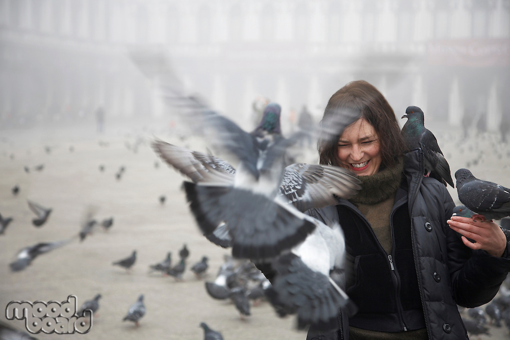 Italy Venice pigeons flying towards female tourist