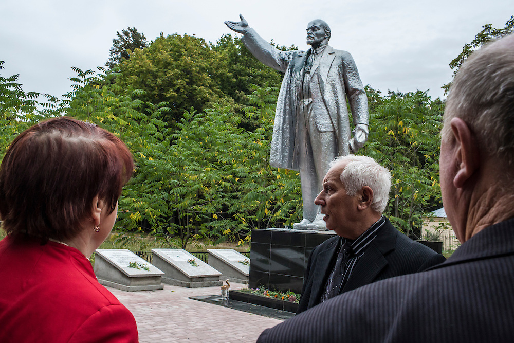 SEMYONOVKA, UKRAINE - SEPTEMBER 13, 2015: Tatyana I. Pus, 68, Ivan M. Papchenko, 67, the secretary of the local Communist party, and Ivan Kovalenko, 69, from left, near a reconstituted statue of Vladimir I. Lenin in Semyonovka, Ukraine. The statue, which was taken down from the town square in the immediate aftermath of the collapse of the government of President Viktor Yanukovych in February 2014, was erected again in a new, more discreet, location in a park two months later based in part by a petition to the city council submitted by the local Communist party. A new decommunization law has stirred criticism as being a diversion from more pressing issues of war and the economy. CREDIT: Brendan Hoffman for The New York Times