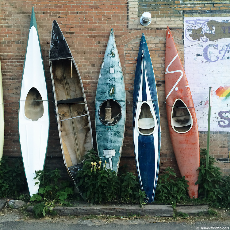 A group of old, vintage kayaks decorate an alleyway in downtown Salida, Colorado.