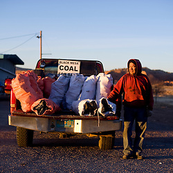 Ronald Begay sells coal on the side of Highway 118 in Gallup, N.M. Begay makes the trip to Black Mesa, Ariz. to purchase coal several times a week, which he then sells at several locations on the reservation.