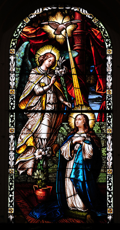 Stained glass image shows the angel Gabriel visiting Mary to announce God has chosen her to give birth to Jesus. From St. Francis Xavier Cathedral in Green Bay. Gabriel's wings are made of peacock feathers, which represent royalty and eternal life. (Photo by Sam Lucero)