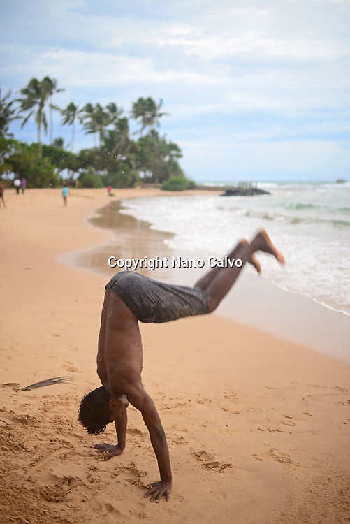 Young man performing acrobatic jumps on Hikkaduwa beach, Sri Lanka