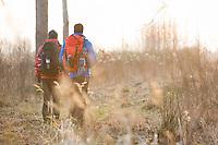 Full length rear view male hikers walking in field