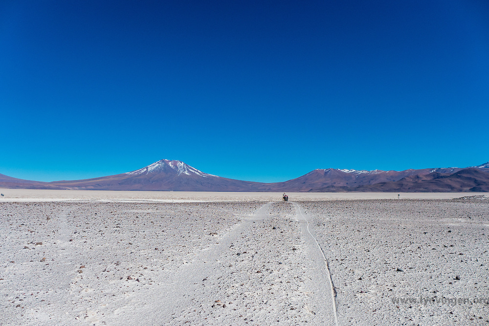 Cyclist pushing his bike in the volcanic ash close to the Volcano Ollage in Chile, Atacama desert, close to the Bolivian border