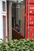 © Licensed to London News Pictures. 09/04/2013. London, UK A man erects a screen to prevent media seeing activity. Boxes are loaded into a shipping container from the North Korean Embassy in Ealing London today 9th April 2013. On Friday North Korea warned it would not be able to guarantee the safety of embassy staff in their country in the event of a war. Photo credit : Stephen Simpson/LNP