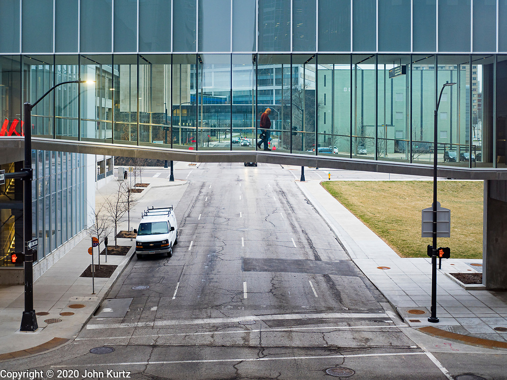 "24 MARCH 2020 - DES MOINES, IOWA: A solitary person walks through the Des Moines skywalk. The city was deserted Tuesday as most people chose to work from home or stay in their homes. On Tuesday morning, 24 March, Iowa reported over 120 confirmed cases of the Coronavirus (SARS-CoV-2) and COVID-19. Restaurants, bars, movie theaters, places that draw crowds are closed for at least 30 days. The Governor has not ordered ""shelter in place""  but several Mayors, including the Mayor of Des Moines, have asked residents to stay in their homes for all but the essential needs. People are being encouraged to practice ""social distancing"" and many businesses are requiring or encouraging employees to telecommute.        PHOTO BY JACK KURTZ"
