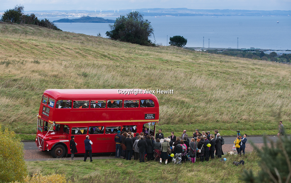 Dave and Gica marry with a Humanist Society Wedding ceremony conducted by celebrant Dorothy Nowak next to their London Routemaster hired from The Red Bus in the Queens Park, Edinburgh with Arthur's Seat in the background. 10th October 2014<br /> <br /> Photograph by Alex Hewitt<br /> alex.hewitt@gmail.com<br /> 07789 871540