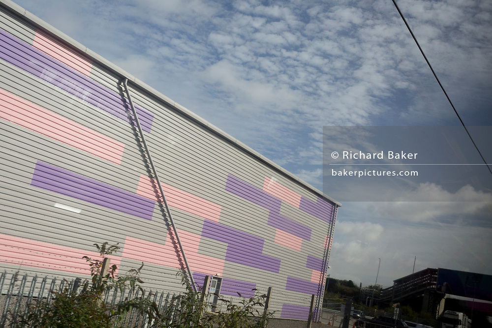 Diagonal lines of an industrial unit alongside the railway line through south Essex, on 8th October 2019, in Dagenham, Essex, England. Voters in Dagenham borough voted 62% in favour of Brexit during the 2016 referendum.
