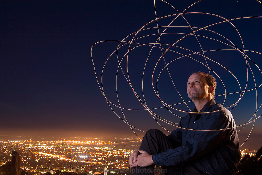 Astronomer Geoff Marcy above the lights of the UC Berkeley Campus surrounded by light trails representing swooping eccentric orbits of exoplanets. Unlike the planets of our solar system, the orbits of most of the exoplanets Marcy and his team have discovered are squashed into shapes more like ovals, footballs, and cigars.