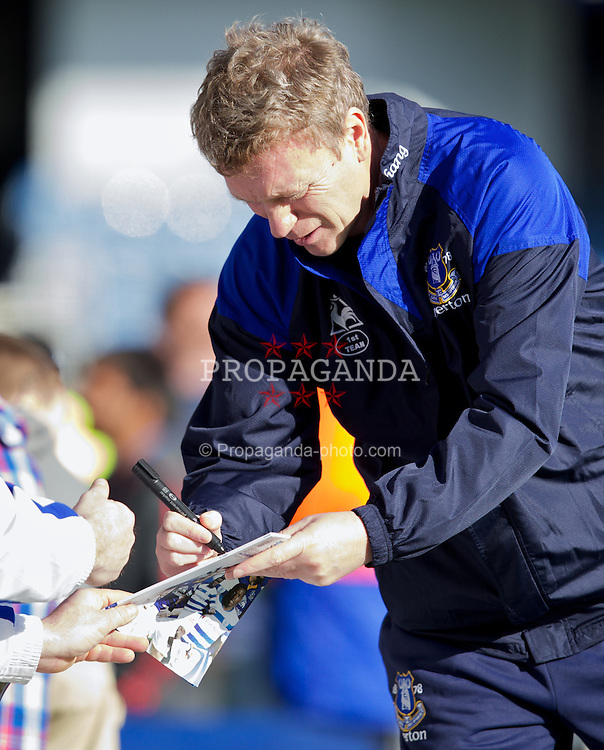 LONDON, ENGLAND - Saturday, March 3, 2012: Everton's manager David Moyes signs his autograh to a fan before the Premiership match against Queens Park Rangers at Loftus Road. (Pic by Vegard Grott/Propaganda)