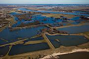 Nederland, Gelderland, Gelderse Poort, 07-03-2010; Gendtse Waard (Gendtse Polder) met rivier de Waal. In het kader van het programma Ruimte voor de Rivier, zijn er plannen om de rivierdijk op verschillende plaatsen te verlagen, evenals kades in de polder. Bij hoog water zou de bocht van de rivier (rechts, gedeeltelijk buiten beeld) zou als het ware afgesneden worden. De maatregelen zouden er voor zorgen dat meer rivierwater naar zee zou stromen (en ook sneller) met een betere waterverdeling tussen Waal en Pannerdensch kanaal..Gendtse Waard (foreland) or Gendt polder situated on the river Waal. Under the program Room for the River, it is considered to cut the river dike / the levee in several places. .This way more river water will flow to the sea (and faster), this provides a better division of the river Rhine, between the Waal and the Pannerdensch Channel. At high waters, the river could flow in a more straight line (towards the viewer)..luchtfoto (toeslag), aerial photo (additional fee required).foto/photo Siebe Swart